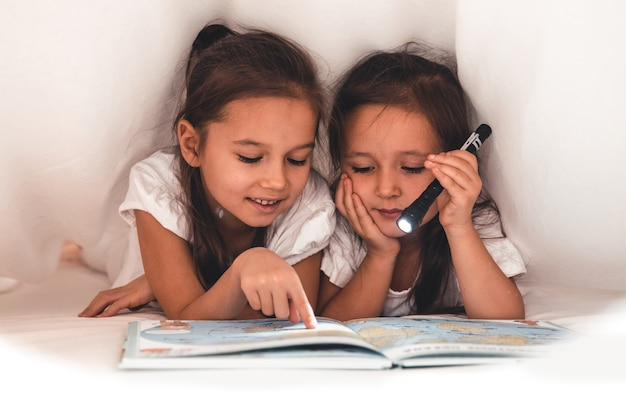 Deux filles lisant sous une couverture