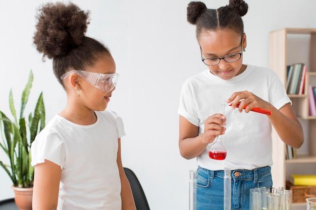 Deux filles avec des lunettes de sécurité portant des expériences scientifiques