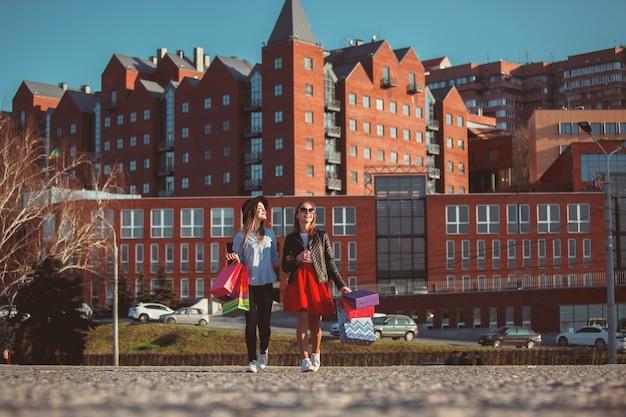 Deux filles marchant avec du shopping dans les rues de la ville