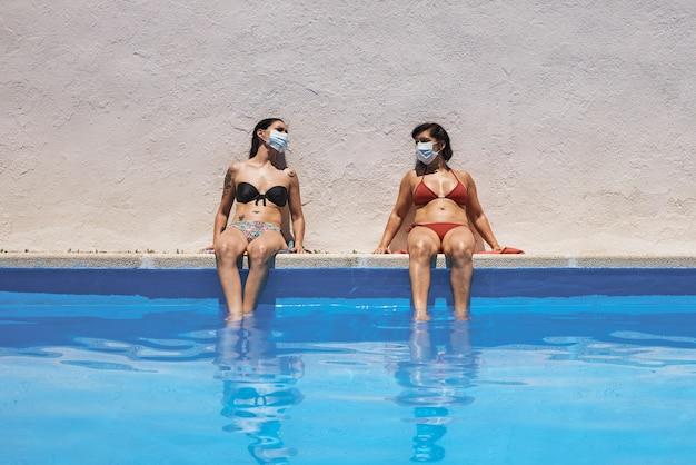 Deux filles avec des masques assis dans la piscine en train de bronzer