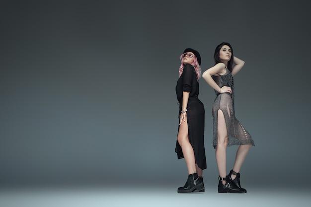 Deux filles à la mode portant des tenues à la mode noires posant