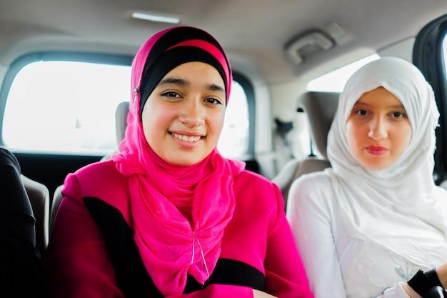 Deux filles musulmanes heureux dans une voiture en voyage