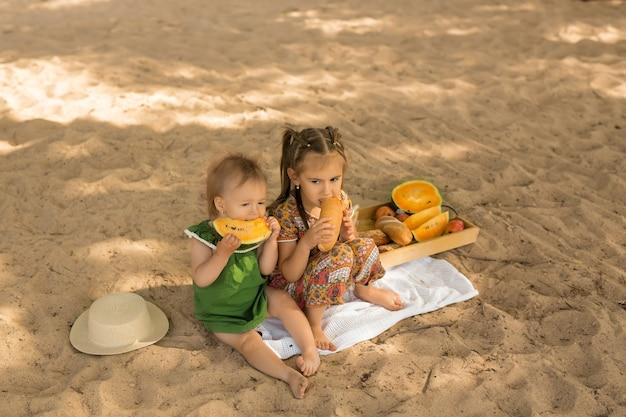Deux filles ont pique-niqué sur une plage de sable
