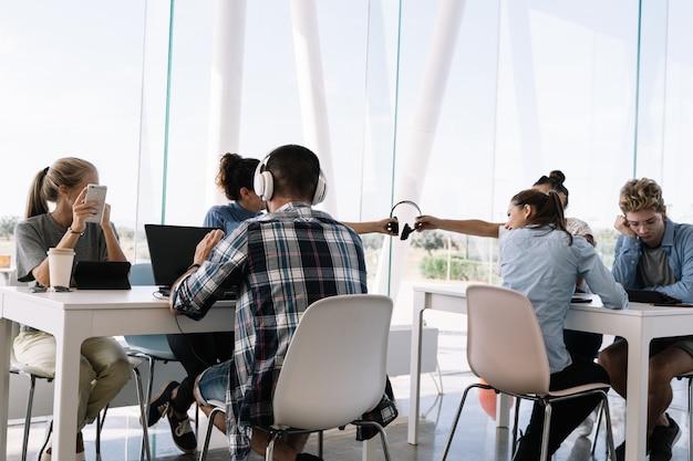 Deux filles partageant des casques assis à des tables de travail avec d'autres personnes dans un coworking