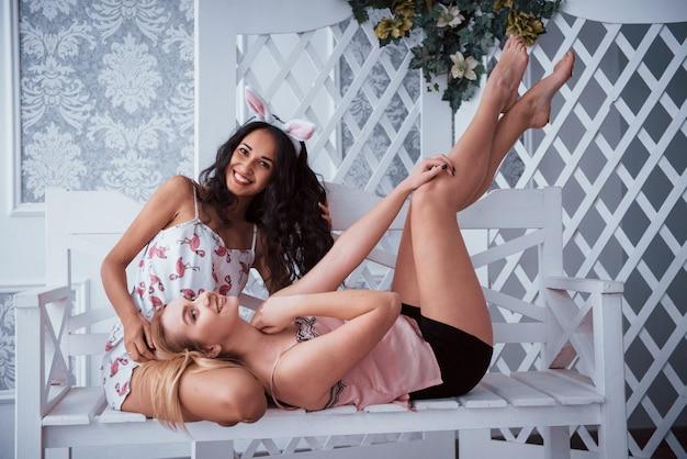 Deux filles à la partie de bachelorette est assis et couché sur le banc blanc