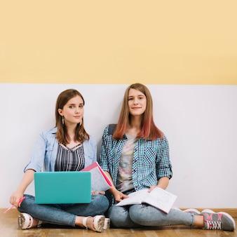 Deux filles posant à la caméra avec des études