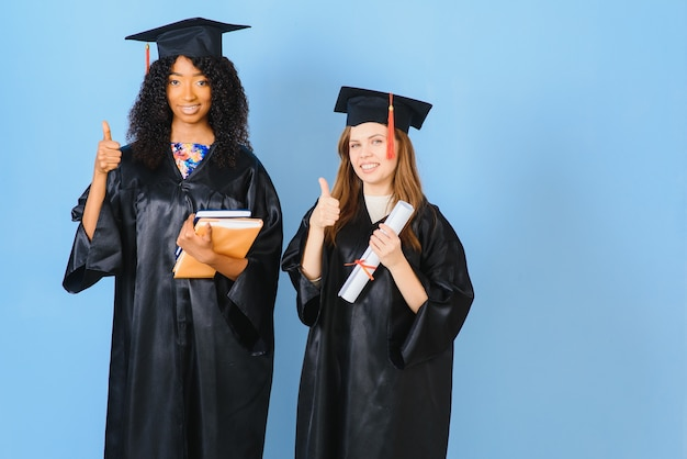 Deux filles posent pour prendre des photos en robes noires et détiennent un certificat de diplôme. ils sont diplômés et titulaires d'un certificat. ils sont heureux et de bonne humeur.