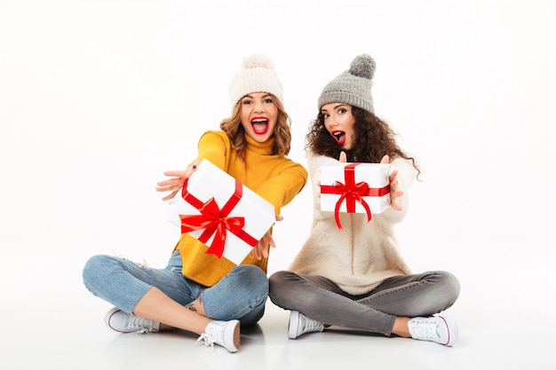 Deux filles qui criaient heureux dans des chandails et des chapeaux assis avec des cadeaux sur le sol ensemble sur un mur blanc
