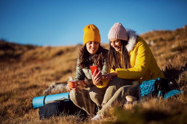 Deux filles en randonnée à l'aide d'un téléphone