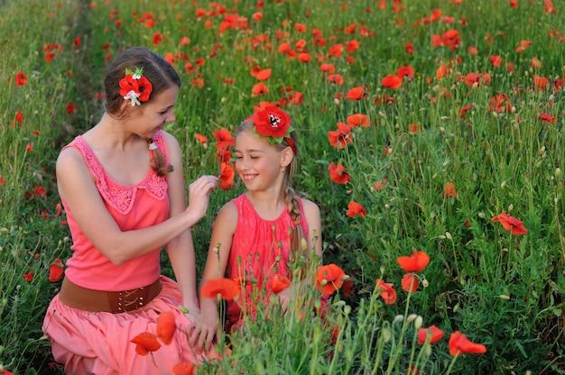 Deux filles en robe rouge marchant sur le champ de coquelicot au printemps