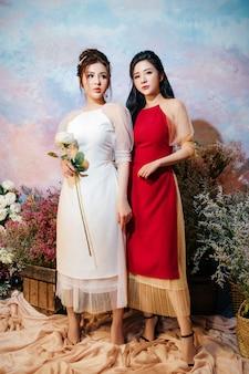 Deux filles avec des robes rouges et blanches debout avec des fleurs