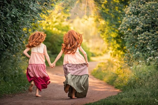 Deux filles rousses en robes longues courent pieds nus le long du chemin du parc vers le coucher du soleil, vue de dos.