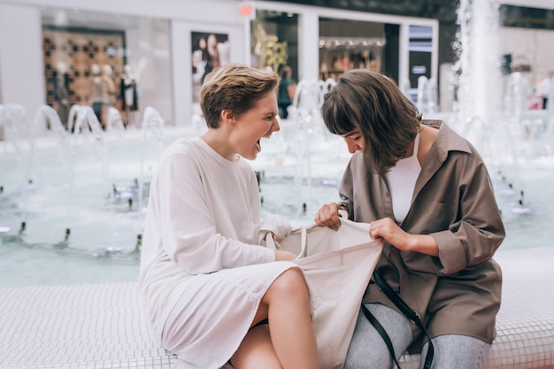 Deux filles s'amusent dans le centre commercial, à côté d'une fontaine