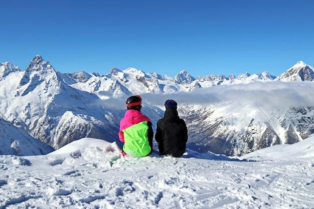 Deux filles s'asseyent au sommet d'une montagne enneigée