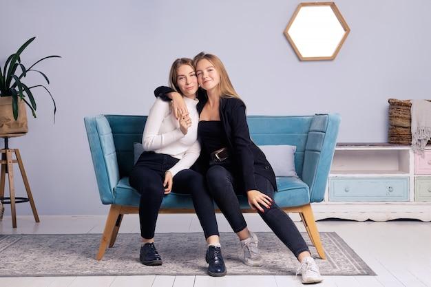Deux filles s'embrassent. ils sont assis sur le canapé à la maison. ils sont de bonne humeur. ils sont contents l'un de l'autre.