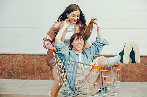 Deux filles se promènent dans la ville et montent dans un chariot.