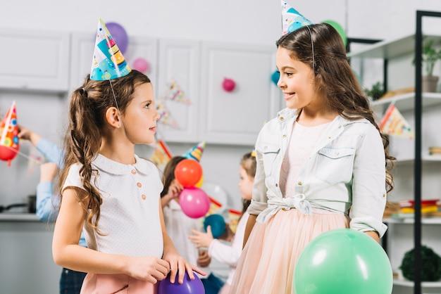 Deux filles se regardant tout en célébrant un anniversaire en cuisine