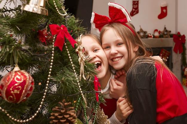 Deux filles se réjouissent et rient dans une robe de noël près d'un arbre de noël décoré