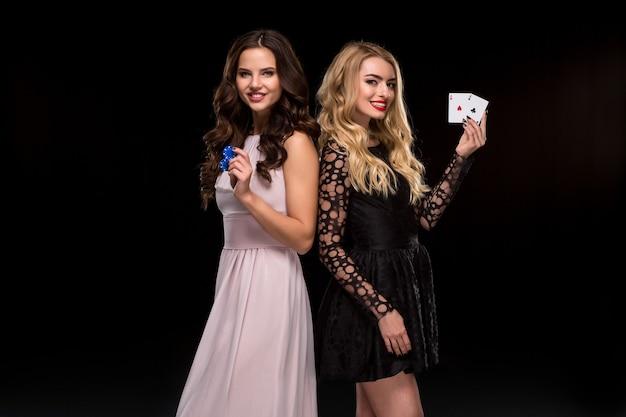 Deux filles sexy brune et blonde, posant avec des jetons et des cartes dans leurs mains, concept de poker. prise de vue en studio. deux belles femmes en robes sur fond noir