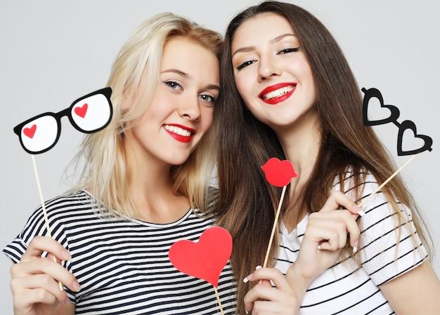Deux filles sexy élégantes meilleurs amis tenant des bâtons de fête en papier