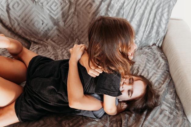 Deux filles, soeurs jouant sur le canapé, câlins, rires, combat, t-shirt