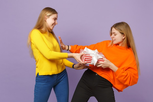 Deux filles de soeurs jumelles blondes drôles dans des vêtements vifs tenant une boîte présente à rayures rouges avec un ruban cadeau isolé sur un mur bleu violet. anniversaire de la famille des gens, concept de vacances.