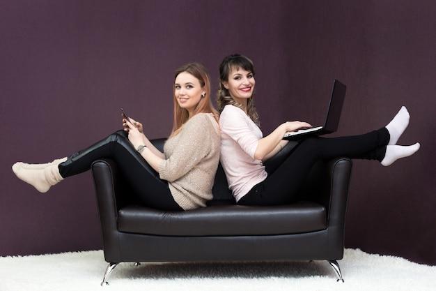 Deux filles sont assises sur le canapé, dos à dos.