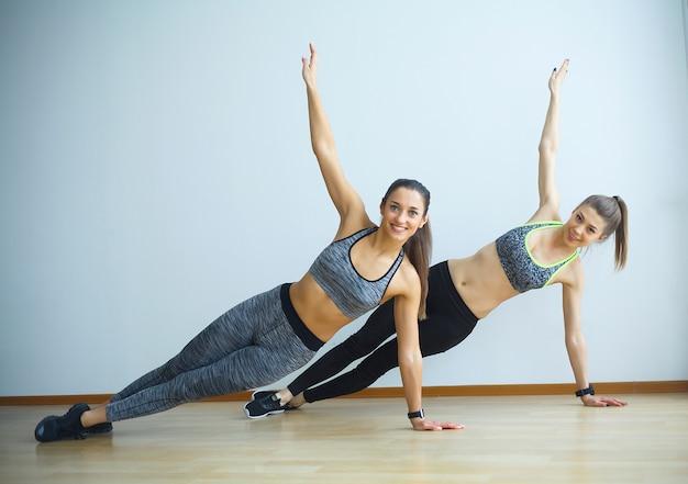 Deux filles sportives font des exercices en salle de gym