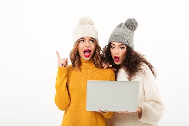 Deux filles surpris en chandails et chapeaux debout ensemble lors de l'utilisation d'un ordinateur portable sur un mur blanc