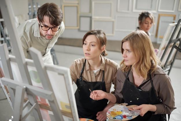 Deux filles en tabliers montrant la peinture sur chevalet à leur professeur pendant la leçon et le consultant au sujet de certains détails