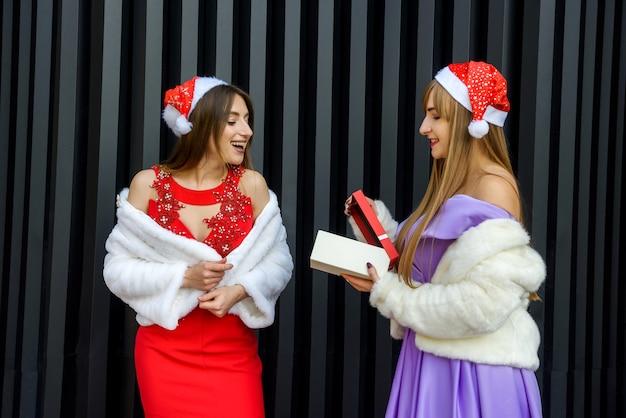 Deux filles tenant une boîte-cadeau. célébration du nouvel an ou de noël ou d'anniversaire. offrir un cadeau