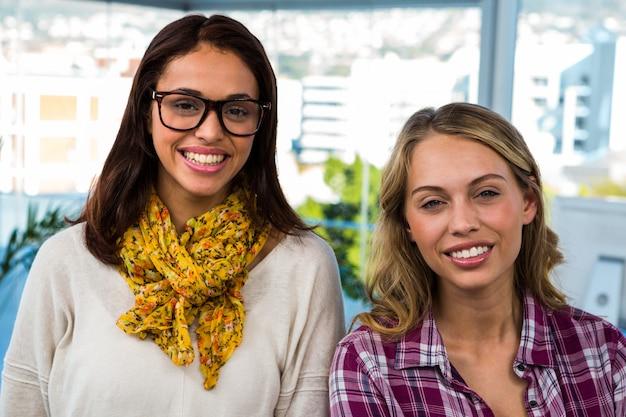 Deux filles travaillent au bureau et souriant