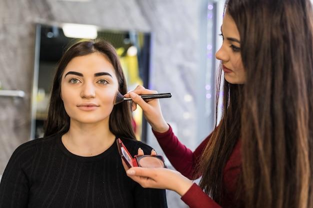 Deux filles travaillent sur le maquillage lumineux du soir