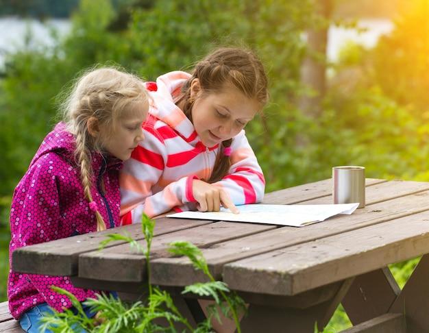 Deux filles voir la carte de s'asseoir sur une table en bois, norvège