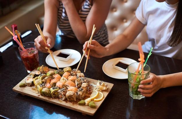 Deux filles yang mangent de délicieux sushis roulants au restaurant servi sur la planche de bois avec des baguettes, de la sauce soja et des cocktails