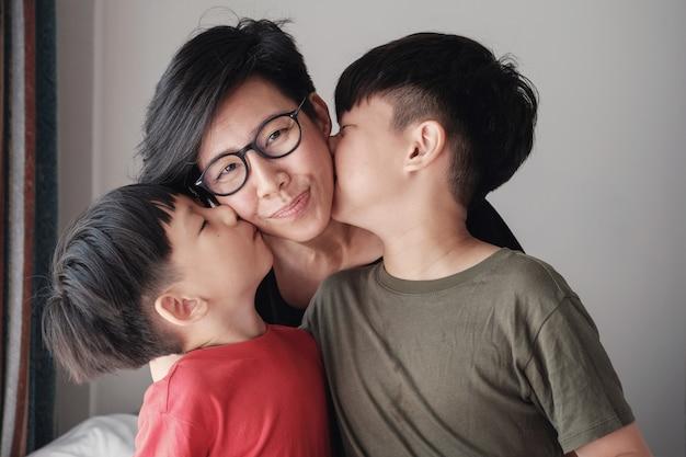Deux fils embrassant leur mère à la maison
