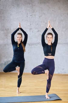 Deux fitnesswomen debout dans la posture de vrksasana.