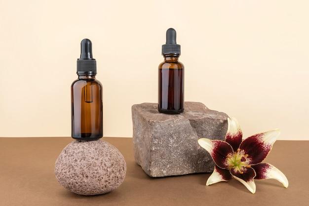 Deux flacons cosmétiques en verre marron avec pipette sur pierres, fond marron beige. concept cosmétique de spa bio naturel. vue de face espace de copie.