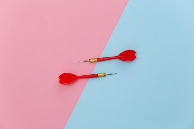 Deux fléchettes en plastique rouge avec pointe en métal sur fond pastel bleu rose.