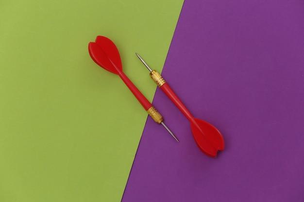 Deux fléchettes en plastique rouge avec pointe en métal sur fond vert violet.