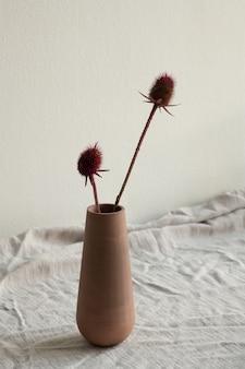 Deux fleurs sauvages sèches avec de longues tiges en argile ou vase fait main en céramique ou pichet debout sur une table recouverte de tissu de lin blanc sur le mur