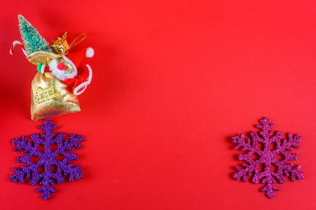 Deux flocons de neige, le père noël avec un sac de cadeaux sur fond de nouvel an.