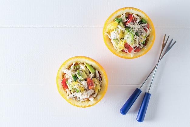 Deux fourchettes et deux moitiés de salade d'orange sur une table en bois blanc
