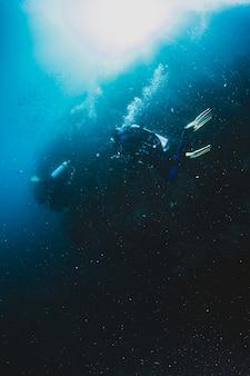 Deux freediverss nageant sous l'eau sur les coraux de corail vivants.
