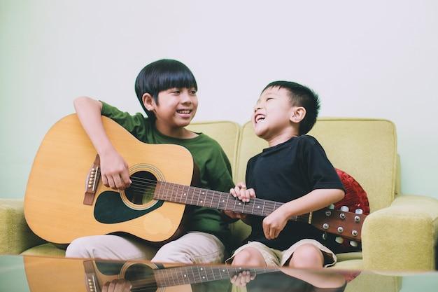Deux frère asiatique s'amusant ensemble en chantant et en jouant de la guitare