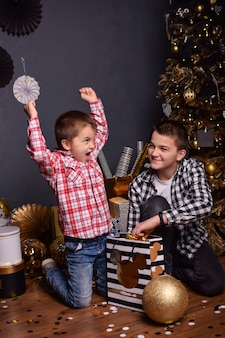 Deux frères adolescents assis sur le sol du salon de noël avec des cadeaux et souriant
