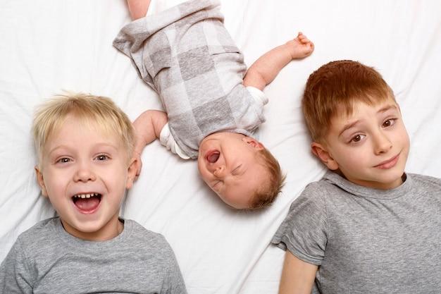 Deux frères aînés et le plus jeune bébé dans un lit blanc. enfance heureuse, grande famille. vue de dessus