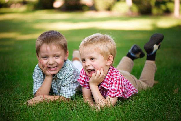 Deux frères allongés sur l'herbe dans un parc en plein air, souriant et