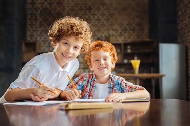 Deux frères aux cheveux bouclés regardant la caméra avec des sourires joyeux sur leurs visages tout en se réunissant à une table et en se rassemblant à la maison.