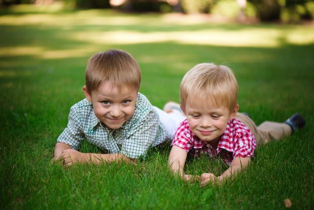 Deux frères, coucher herbe, dans parc, dehors, sourire, et